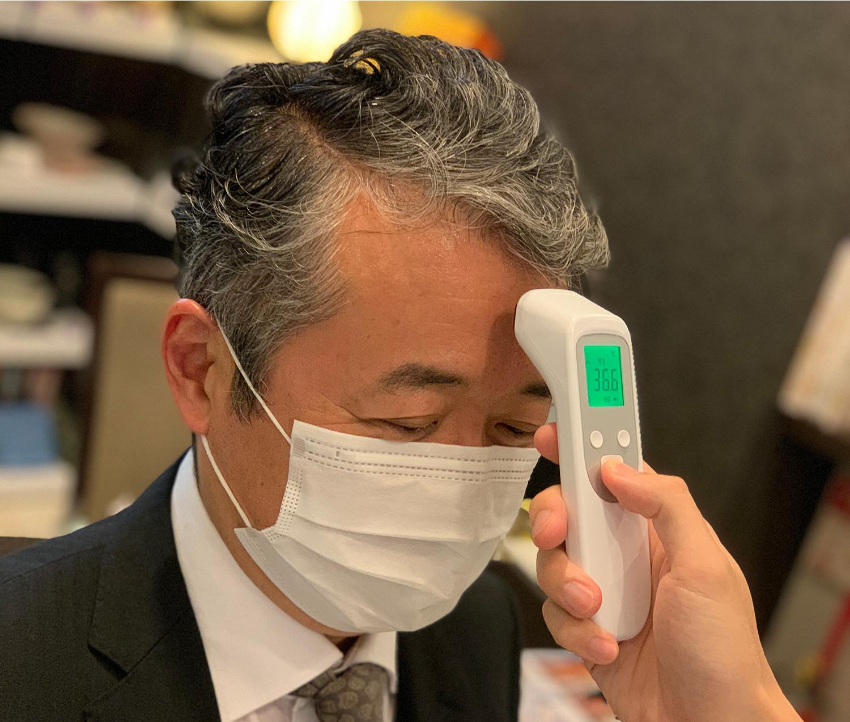 従業員通用口に非接触型体温計を設置し、体温の確認と手指の消毒を徹底しております
